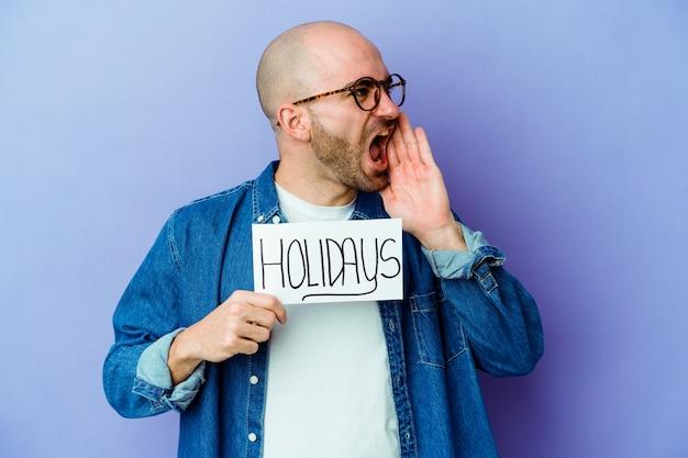 Молодой кавказский лысый мужчина держит праздничный плакат, изолированный на синей стене, кричит и держит ладонь возле открытого рта.