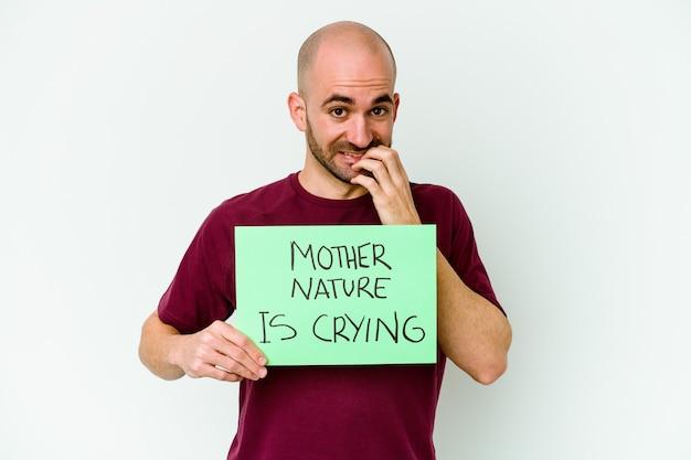 指の爪を噛んで、神経質で非常に心配している白い背景で孤立して泣いている母なる自然を保持している若い白人のハゲ男。