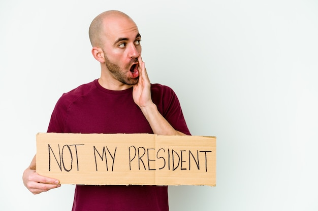 白い背景で隔離された私の大統領ではないプラカードを持っている若い白人のハゲ男は秘密の熱いブレーキングニュースを言って脇を見ています