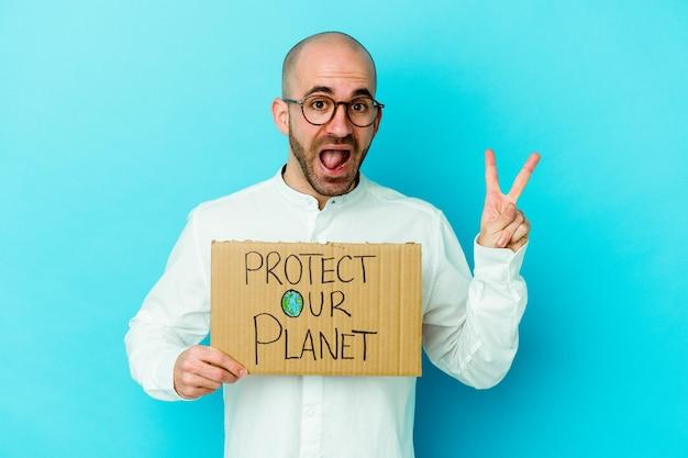 紫色の背景に分離された私たちの惑星のプラカードを保持している若い白人のハゲ男は、指で平和のシンボルを喜んで気楽に示しています。