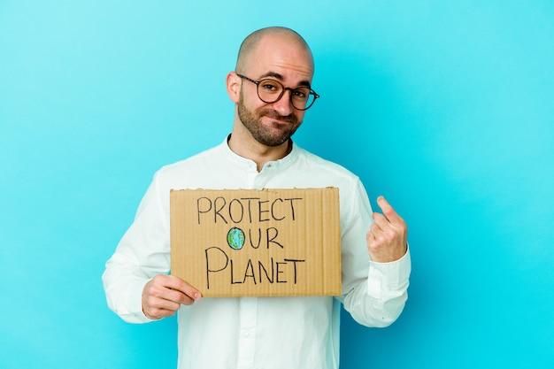 紫色の背景に分離された私たちの惑星のプラカードを持っている若い白人のハゲ男は、招待が近づくようにあなたに指を指しています。