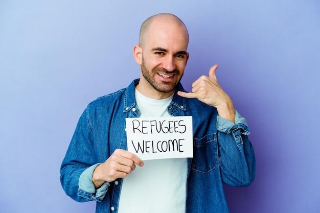 젊은 백인 대머리 남자 손가락으로 휴대 전화 제스처를 보여주는 파란색 배경에 고립 난민 환영 현수막을 들고.