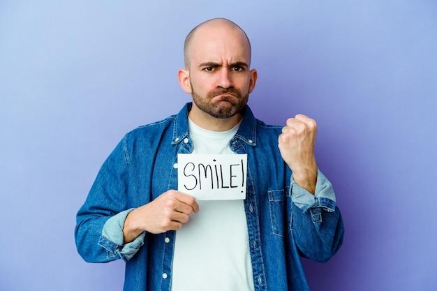 Молодой кавказский лысый мужчина держит плакат улыбки, изолированный на фиолетовой стене, показывая кулак в камеру, агрессивное выражение лица.