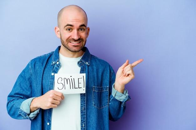 Молодой кавказский лысый мужчина держит плакат улыбки, изолированный на фиолетовой стене, улыбаясь и указывая в сторону, показывая что-то на пустом месте.