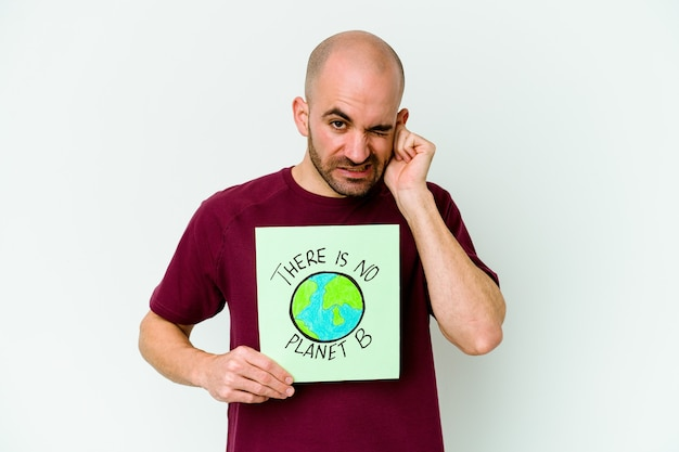 Молодой кавказский лысый мужчина, держащий не планету b, изолированный на фиолетовой стене, закрывающей уши руками.