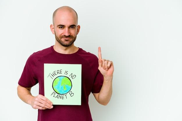 젊은 백인 대머리 남자는 손가락으로 번호 하나를 보여주는 보라색 벽에 고립 된 행성 b 플래 카드가 없습니다