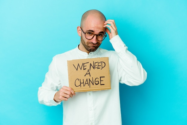Молодой кавказский лысый мужчина держит плакат с надписью «нам нужны перемены», изолированный на фиолетовом фоне. в шоке, она вспомнила важную встречу.