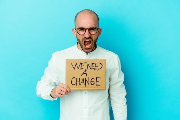Молодой кавказский лысый мужчина держит плакат с надписью «нам нужно изменение», изолированный на фиолетовом фоне, кричащий очень сердито и агрессивно.
