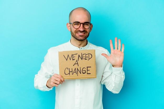 Молодой кавказский лысый мужчина держит табличку с надписью «нам нужно изменение» на фиолетовом фоне, улыбаясь, весело показывая номер пять с пальцами.