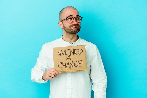 保持している若い白人のハゲ男私たちは目標と目的を達成することを夢見て紫色の壁に分離された変更プラカードが必要です