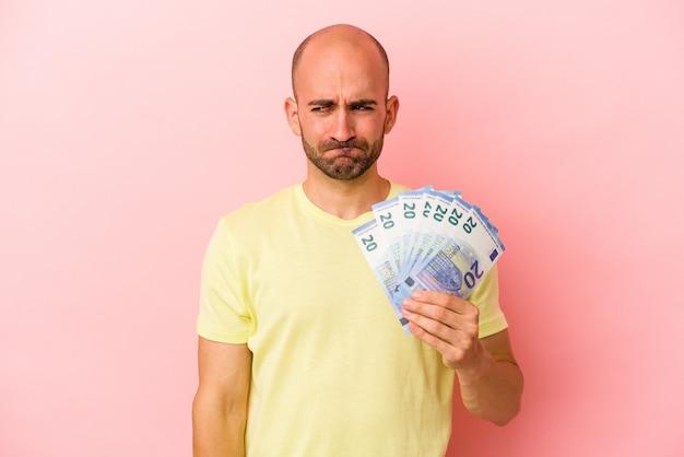 분홍색 배경에 격리된 지폐를 들고 있는 백인 대머리 청년은 혼란스럽고 의심스럽고 확신이 서지 않습니다.