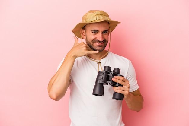 Молодой кавказский лысый мужчина держит бинокль на розовом фоне, показывая жест мобильного телефона пальцами.