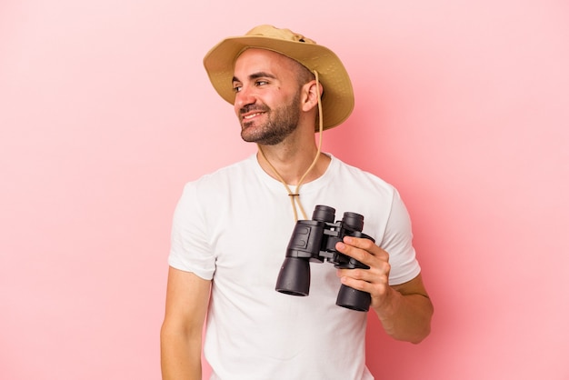 Young caucasian bald man holding binoculars isolated on pink background  looks aside smiling, cheerful and pleasant.