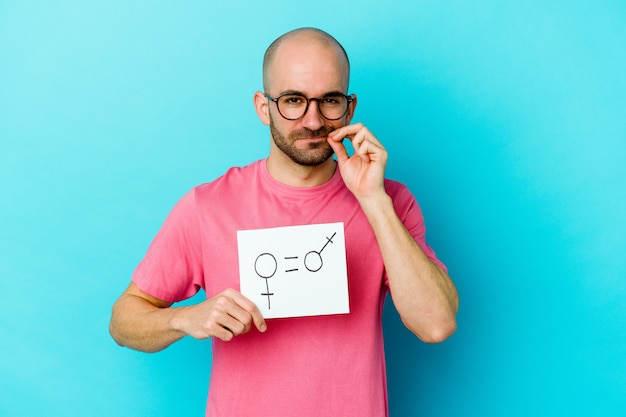 Young caucasian bald man holding a equality gender placard isolated on yellow background with fingers on lips keeping a secret.