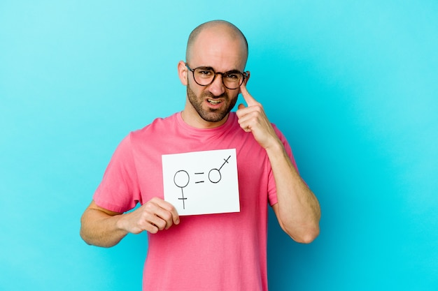 Young caucasian bald man holding a equality gender placard isolated on yellow wall showing a disappointment gesture with forefinger.
