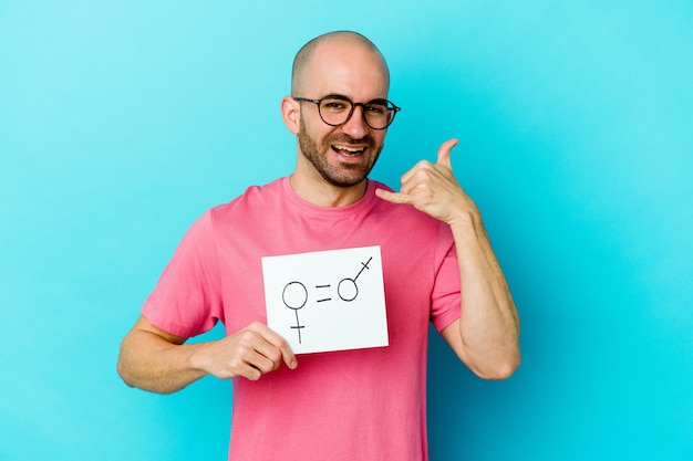 Young caucasian bald man holding a equality gender placard isolated on yellow wall showing a mobile phone call gesture with fingers.