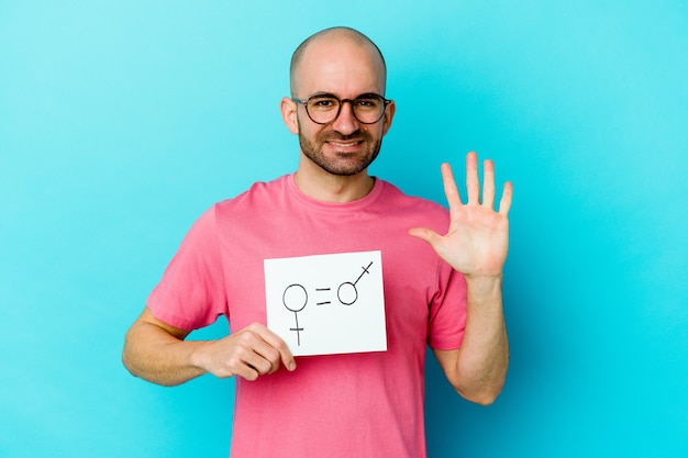 Young caucasian bald man holding a equality gender placard isolated on yellow wall smiling cheerful showing number five with fingers.