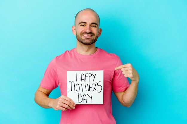 Young caucasian bald man holding a happy mothers day placard isolated on blue wall person pointing by hand to a shirt copy space, proud and confident