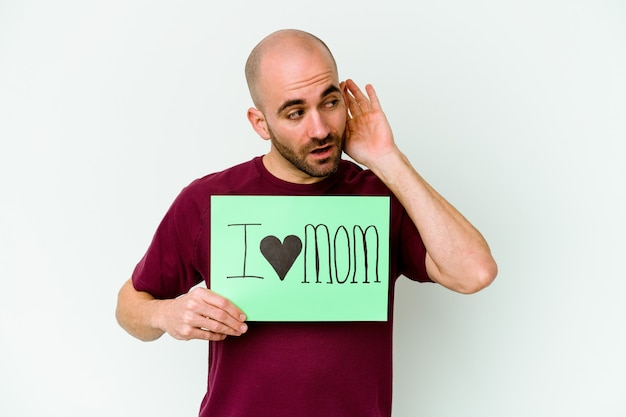 Young caucasian bald man holding a i love mom placard isolated on yellow wall trying to listening a gossip.