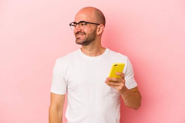 Young caucasian bald man holding mobile phone isolated on pink background  looks aside smiling, cheerful and pleasant.