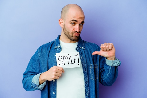 Young caucasian bald man holding a smile placard isolated on purple wall feels proud and self confident, example to follow.