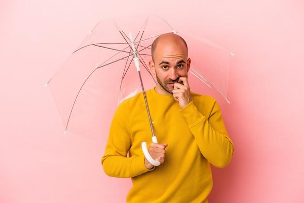 ピンクの背景に孤立した傘を持っている若い白人のハゲ男は、神経質で非常に不安な指の爪を噛んでいます。