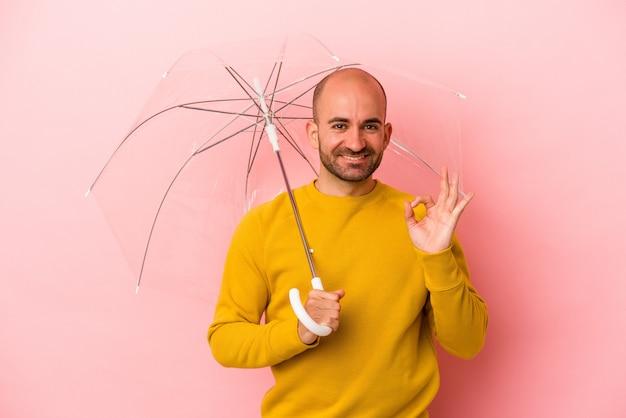 ピンクの背景に孤立した傘を持っている若い白人のハゲ男は、陽気で自信を持って大丈夫なジェスチャーを示しています。