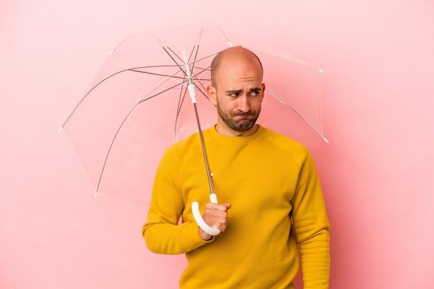 분홍색 배경에 격리된 우산을 들고 있는 백인 대머리 청년은 혼란스럽고 의심스럽고 확신이 서지 않습니다.