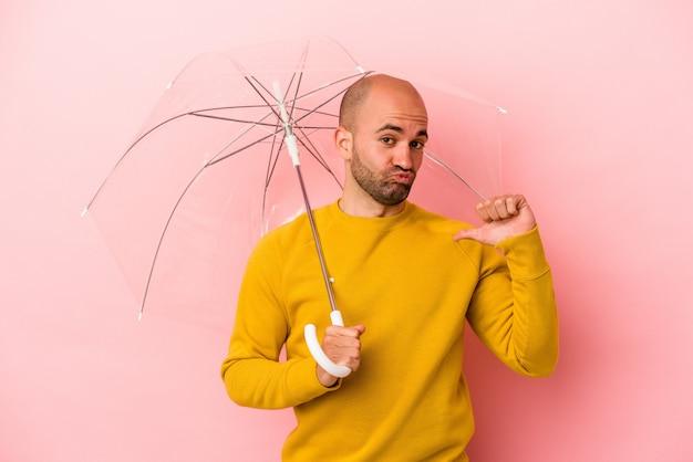 ピンクの背景に分離された傘を持っている若い白人のハゲ男は、誇りと自信を持って、従うべき例を感じます。