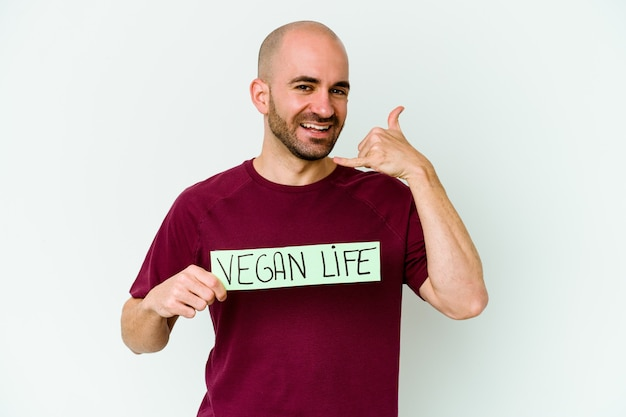 Young caucasian bald man holding a vegan life placard isolated on purple wall showing a mobile phone call gesture with fingers.