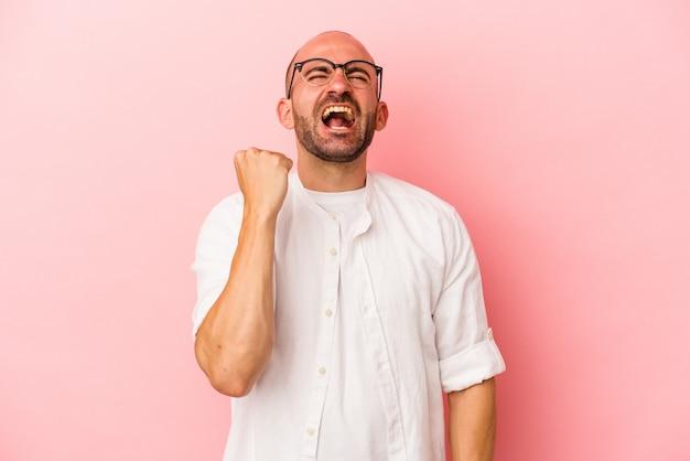 勝利、情熱と熱意、幸せな表現を祝うピンクの背景に分離された若い白人のハゲ男。