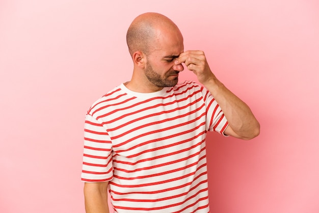 顔の正面に触れて、頭痛を持っているピンクの背景に分離された若い白人のハゲ男。