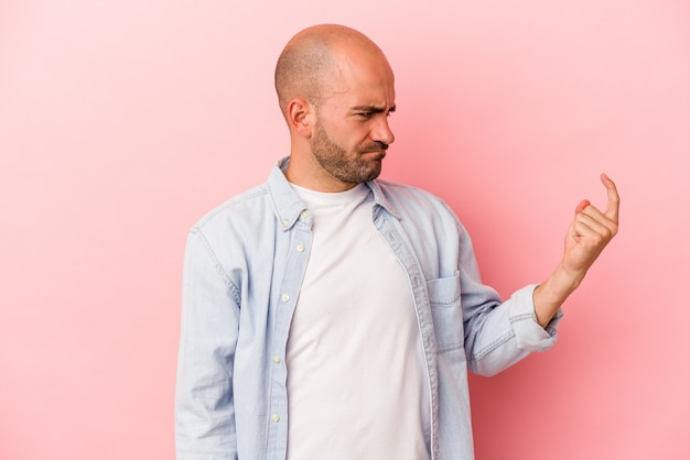 ピンクの背景に孤立した若い白人のハゲ男が、誘うようにあなたに指を向けて近づいています。