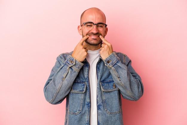 Молодой кавказский лысый мужчина на розовом фоне улыбается, указывая пальцами на рот.