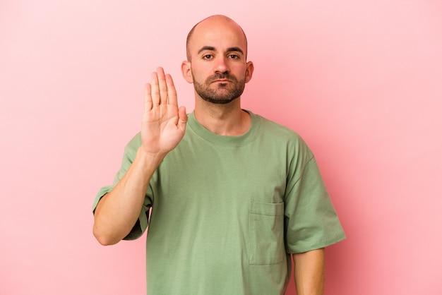 분홍색 배경에 고립된 젊은 백인 대머리 남자는 손을 뻗은 채 정지 신호를 보여주며 당신을 방해합니다.