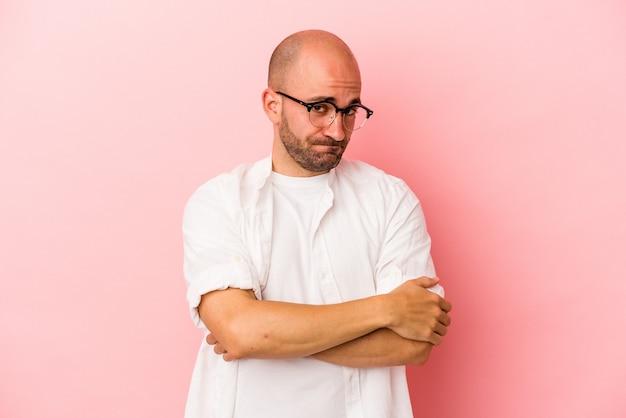 분홍색 배경에 고립된 젊은 백인 대머리 남자는 비꼬는 표정으로 카메라를 쳐다보며 불행합니다.