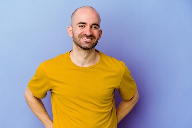 紫色の背景で隔離の若い白人ハゲ男幸せ、笑顔、陽気な。