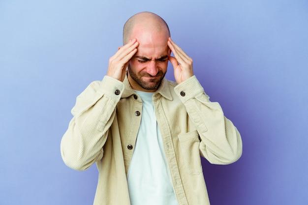 Молодой кавказский лысый мужчина изолирован на фиолетовом фоне, трогательно висках и имея головную боль.