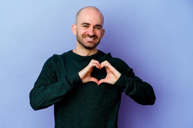Молодой кавказский лысый мужчина изолирован на фиолетовом, улыбаясь и показывая руками форму сердца.
