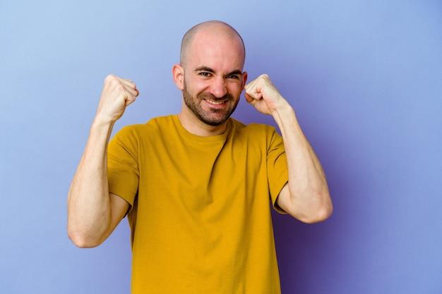 Молодой кавказский лысый мужчина изолирован на фиолетовой стене, танцует и веселится Premium Фотографии