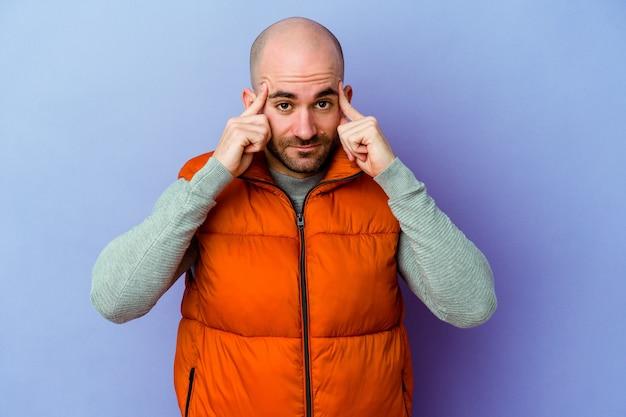 Молодой кавказский лысый мужчина, изолированный на фиолетовой стене, сосредоточился на задаче, держа указательные пальцы, указывая головой.