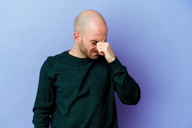 젊은 백인 대머리 남자는 얼굴의 전면을 만지고, 머리가 아파 보라색 벽에 고립