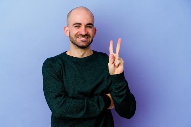 指で2番目を示す紫色の壁に分離された若い白人のハゲ男。