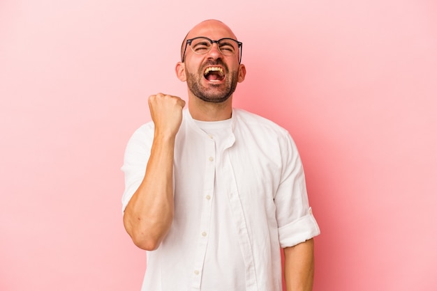 Young caucasian bald man isolated on pink background  celebrating a victory, passion and enthusiasm, happy expression.