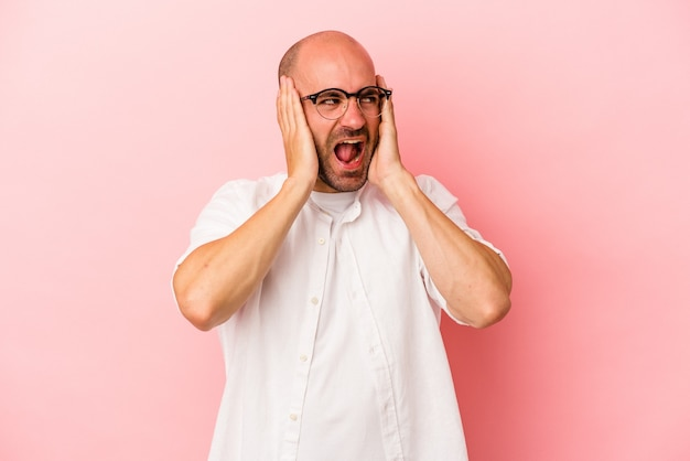 Young caucasian bald man isolated on pink background  covering ears with hands trying not to hear too loud sound.