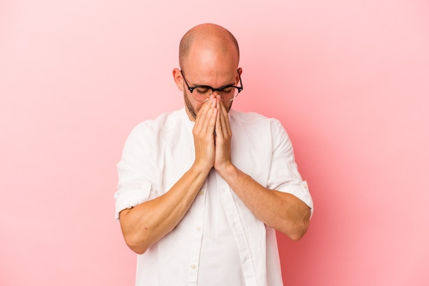 Young caucasian bald man isolated on pink background  praying, showing devotion, religious person looking for divine inspiration.