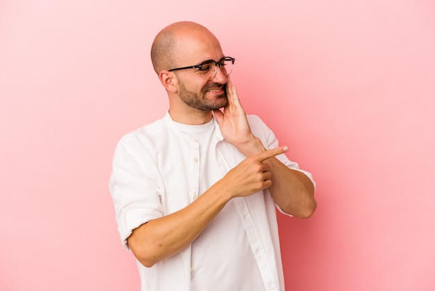 Young caucasian bald man isolated on pink background  saying a gossip, pointing to side reporting something.