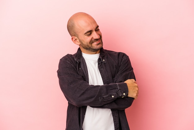 Young caucasian bald man isolated on pink background  smiling confident with crossed arms.