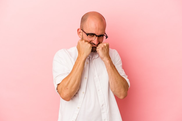 Young caucasian bald man isolated on pink background  throwing a punch, anger, fighting due to an argument, boxing.