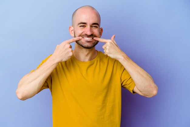 Young caucasian bald man isolated on purple background smiles, pointing fingers at mouth.